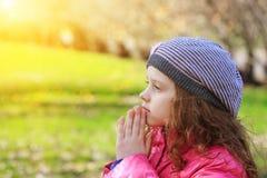 Praying child in spring park. Praying little girl in spring park Stock Photo