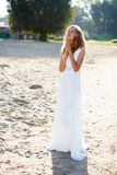 Praying dear girl bride  in a white dress on the sunny outdoor Stock Photo