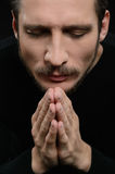 Praying with eyes closed. Devout bearded man praying and holding. His hands clasped while isolated on black royalty free stock image