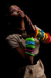 Praying with faith. Young african american praying in dim light Royalty Free Stock Photography