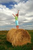 Praying Farm Girl. A farm girl prays on top of a straw bale Stock Images