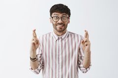 Praying for favorite sportsman to win. Excited good-looking caucasian male model in black glasses and striped shirt. Crossing fingers for good luck clenching stock images