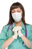 Praying female medical doctor with mask isolated Stock Photography