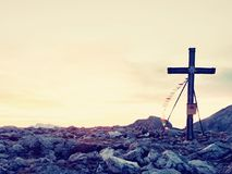 Praying flags fluttering  in the wind on the summit cross. Wooden crucifix on top of Alpine mountain Royalty Free Stock Photography