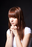 The praying girl. On a black background Stock Photo