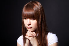 The praying girl. On a black background Royalty Free Stock Images