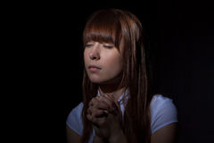 The praying girl. On a black background Royalty Free Stock Photography