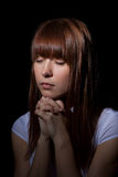 The praying girl. On a black background Stock Photos