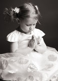 Praying girl. Praying little girl on gray background Stock Photos
