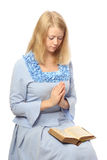 Praying girl with a bible. On her lap, isolated on white background Royalty Free Stock Photo