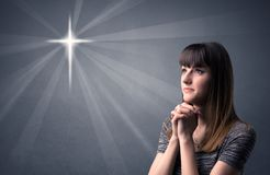 Praying girl concept. Young woman praying on a grey background with a shiny cross silhouette above her Royalty Free Stock Photo