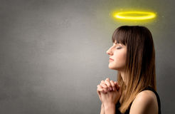 Praying girl concept. Young woman praying on a grey background with a shiny yellow halo above her head stock images