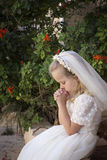 Praying girl first holy communion. A young child praying during her first holy communion royalty free stock images