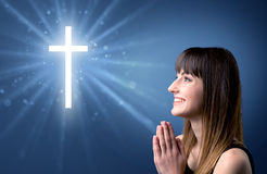 Praying girl. Young woman praying on a blue background with a sparkling cross above her Royalty Free Stock Photos