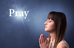Praying girl. Young woman praying on a blue background with the word Pray written above her Royalty Free Stock Photos