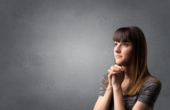 Praying girl. Young woman praying on a grey background Stock Photography