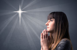 Praying girl. Young woman praying on a grey background with a shiny cross silhouette above her Stock Photography