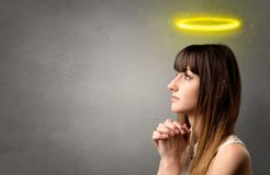 Praying girl. Young woman praying on a grey background with a shiny yellow halo above her head Stock Photography