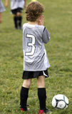 Praying for a goal. A boy playing soccer, praying for a goal Stock Image