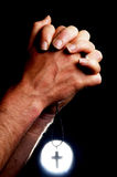 Praying Hands. Holding a cross in front of a bright light Royalty Free Stock Image