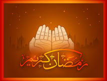 Praying hands with Arabic text for Ramadan. Praying human hands with Arabic Islamic Calligraphy of text Ramadan Kareem on Mosque silhouetted background Stock Photos