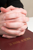 Praying Hands On Bible Stock Photo