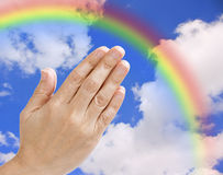 Praying hands with a blue sky and rainbow. Praying hands against the rainbow and clouds Royalty Free Stock Image