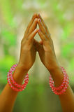 Praying hands of a child. Against green garden background stock photos