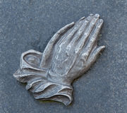 Praying hands on the grave. Hands on the grave of stone Stock Photo