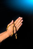 Praying Hands holding rosary beads on black background.  Royalty Free Stock Images