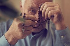 Praying hands of an old man holding rosary beads. Senior man prays for peace in his country stock photos