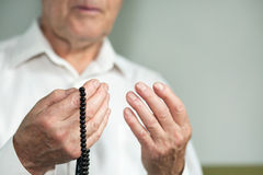 Praying hands of an old man holding rosary beads Royalty Free Stock Images