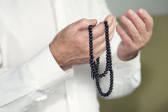 Praying hands of an old man holding rosary beads Stock Image