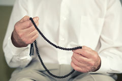 Praying hands of an old man holding rosary beads Stock Photo