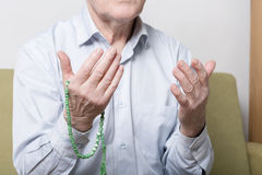 Praying hands of an old man holding rosary beads Stock Photography
