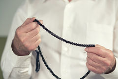 Praying hands of an old man holding rosary beads Royalty Free Stock Photography