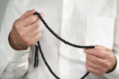 Praying hands of an old man holding rosary beads Stock Images