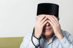 Praying hands of an old man with rosary beads closing eyes Stock Images