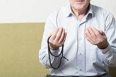 Praying hands of an old man with rosary beads Stock Photo