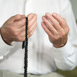 Praying hands of an old man with rosary beads Stock Images