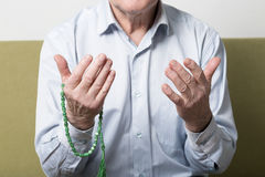 Praying hands of an old man with rosary beads Royalty Free Stock Photo