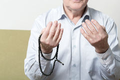 Praying hands of an old man with rosary beads Royalty Free Stock Photos