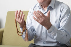 Praying hands of an old man with rosary beads Royalty Free Stock Images