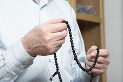 Praying hands of an old man with rosary beads Royalty Free Stock Photography