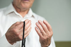 Praying hands of an old man with rosary beads Royalty Free Stock Image