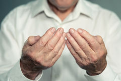Praying hands of an old man Stock Photo