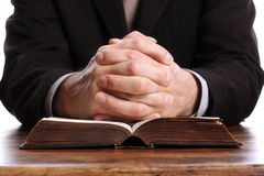 Praying hands on an open bible stock photography