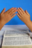 Praying hands over the bible Stock Photos