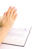 Praying hands over bible. Isolated on a white background Royalty Free Stock Photo