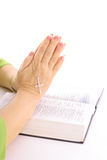 Praying hands over bible with rhinestone cross. Isolated on a white background Stock Image